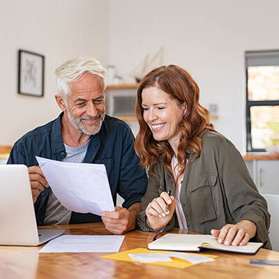 Mature smiling couple sitting and managing expenses at home. Happy senior man and mid woman paying bills and managing budget. Middle aged couple checking accountancy and bills while looking at receipt.